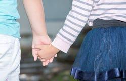 Αδελφός και αδελφές που κρατούν χέρι-χέρι Στοκ Εικόνες