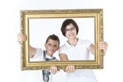 Αδελφός και αδελφή με το πλαίσιο εικόνων μπροστά από τους Στοκ εικόνες με δικαίωμα ελεύθερης χρήσης