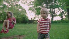 Αδελφός και αδελφή παιδιών στο πάρκο Δύο παιδάκια που κάθονται στο πάρκο 4k φιλμ μικρού μήκους