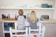 Αδελφός και αδελφή που γονατίζουν στις καρέκλες που πλένουν επάνω, πίσω άποψη Στοκ εικόνες με δικαίωμα ελεύθερης χρήσης