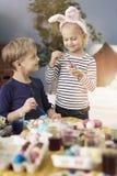 Αδελφός και αδελφή που χρωματίζουν τα αυγά Πάσχας στοκ εικόνες