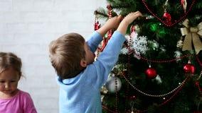 Αδελφός και αδελφή δύο παιδάκι που διακοσμούν το χριστουγεννιάτικο δέντρο στην ημέρα φιλμ μικρού μήκους