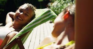 Αλληλεπίδραση δύο γυναικών η μια με την άλλη κάνοντας ηλιοθεραπεία κοντά στην πισίνα απόθεμα βίντεο