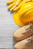 Αδιάβροχα δαντελλών προστατευτικά γάντια καπέλων μποτών σκληρά στον ξύλινο πίνακα Στοκ Εικόνες