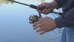 Αλιεία με την περιστροφή Κλείστε επάνω των ανθρώπινων χεριών που τυλίγουν σε έναν πόλο αλιείας φιλμ μικρού μήκους