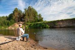Αλιεία στον ποταμό σε μια αγροτική θέση μια θερινή ημέρα Στοκ Εικόνες