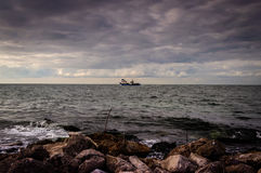 Αλιευτικό σκάφος που πλέει με τον ορίζοντα Στοκ Εικόνες