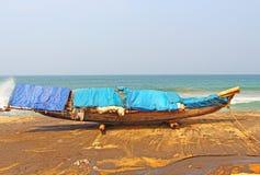 Αλιευτικό σκάφος σε μια μαύρη παραλία Varkala Ινδία Στοκ Εικόνες