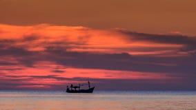 Αλιευτικό σκάφος στα κόκκινα σύννεφα οριζόντων στο σκοτεινό ουρανό μετά από το ηλιοβασίλεμα φιλμ μικρού μήκους