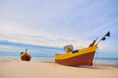 Αλιευτικό σκάφος στην αμμώδη παραλία της θάλασσας της Βαλτικής με το δραματικό ουρανό κατά τη διάρκεια του καλοκαιριού στοκ εικόνες με δικαίωμα ελεύθερης χρήσης