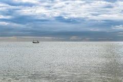 Αλιευτικό σκάφος στη θάλασσα σχεδίων με το νεφελώδη ουρανό Στοκ φωτογραφία με δικαίωμα ελεύθερης χρήσης