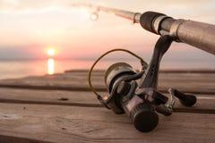 Αλιεύοντας εξέλικτρο και ράβδος που βρίσκονται στην ξύλινη αποβάθρα πέρα από τη λίμνη ηλιοβασιλέματος Στοκ φωτογραφία με δικαίωμα ελεύθερης χρήσης
