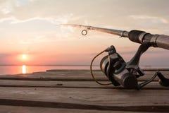 Αλιεύοντας εξέλικτρο και ράβδος που βρίσκονται στην ξύλινη αποβάθρα πέρα από τη λίμνη ηλιοβασιλέματος Στοκ εικόνα με δικαίωμα ελεύθερης χρήσης