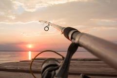 Αλιεύοντας εξέλικτρο και ράβδος που βρίσκονται στην ξύλινη αποβάθρα πέρα από τη λίμνη ηλιοβασιλέματος Στοκ εικόνες με δικαίωμα ελεύθερης χρήσης