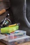 Αλιεύοντας εξοπλισμοί και λαστιχένιες μπότες στον πίνακα ξυλείας Στοκ Φωτογραφίες
