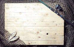 Αλιεύοντας εξοπλισμός και ξηρά ακόμα-ζωή ψαριών στο ξύλινο backgroun Στοκ Εικόνα
