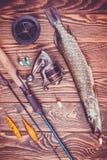 Αλιεύοντας εξοπλισμός και λούτσοι σε έναν ξύλινο πίνακα Στοκ Φωτογραφία