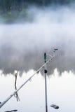 Αλιεύοντας τη ράβδο στην ομιχλώδη λίμνη νωρίς το πρωί, αυγή, πρώτες ακτίνες του ήλιου Έννοια των εποχών, περιβάλλον, οικολογία Στοκ Εικόνες