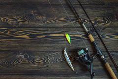 Αλιεύοντας τον εξοπλισμό - περιστροφή, γραμμή, γάντζοι και θέλγητρα στο αγροτικό ξύλινο υπόβαθρο στοκ φωτογραφίες