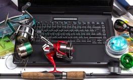 Αλιεύοντας τους εξοπλισμούς στο πληκτρολόγιο ένα μαύρο σημειωματάριο Στοκ εικόνα με δικαίωμα ελεύθερης χρήσης