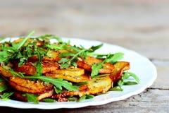 Αλμυρές ψημένες πατάτες με το arugula σε ένα άσπρο πιάτο Ξύλινη ανασκόπηση Στοκ Φωτογραφίες