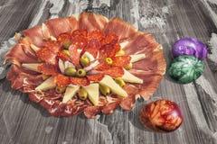 Αλμυρό γαστρονομικό πιάτο Meze ορεκτικών με τα ζωηρόχρωμα βαμμένα αυγά Πάσχας που τίθενται στην παλαιά ξεπερασμένη ραγισμένη επιφ Στοκ εικόνα με δικαίωμα ελεύθερης χρήσης