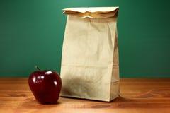 Α πίσω στο σάκο και τη Apple σχολικού μεσημεριανού γεύματος Στοκ Φωτογραφίες
