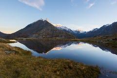 Αλπική λίμνη μεγάλου υψομέτρου στο ειδυλλιακό έδαφος με την αντανάκλαση των μεγαλοπρεπών δύσκολων αιχμών βουνών που καίγονται στο Στοκ φωτογραφίες με δικαίωμα ελεύθερης χρήσης