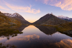 Αλπική λίμνη μεγάλου υψομέτρου στο ειδυλλιακό έδαφος με την αντανάκλαση των μεγαλοπρεπών δύσκολων αιχμών βουνών που καίγονται στο Στοκ εικόνες με δικαίωμα ελεύθερης χρήσης