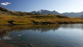 Αλπική λίμνη μεγάλου υψομέτρου στο ειδυλλιακό τοπίο που καλύπτεται μιά φορά από τους παγετώνες Αντανάκλαση της χιονοσκεπούς σειρά φιλμ μικρού μήκους
