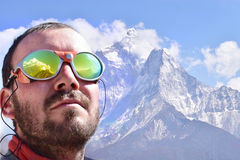 Αλπινιστής που εξετάζει την κορυφή, υπόβαθρο βουνών Στοκ Εικόνες