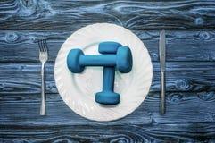 Αλτήρες, σφαίρα και αποσυμπιεστής σε ένα πιάτο ως πρόγευμα, έννοια του υγιούς τρόπου ζωής Στοκ Εικόνες