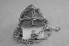 Αλυσίδα που τυλίγεται γύρω από έναν όμορφο ένα μικρό πρότυπο σπίτι φιαγμένο από έγγραφο σε γραπτό Στοκ Εικόνες