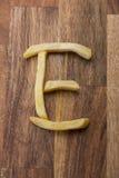 Αλφάβητο Ε τηγανιτών πατατών στο ξύλινο υπόβαθρο Στοκ εικόνες με δικαίωμα ελεύθερης χρήσης