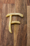 Αλφάβητο Φ τηγανιτών πατατών στο ξύλινο υπόβαθρο Στοκ Εικόνες