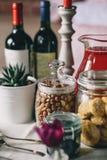 Βάζα γυαλιού με τα φουντούκια, τα μπισκότα και mors, το δοχείο λουλουδιών και το μπουκάλι του κρασιού Στοκ εικόνες με δικαίωμα ελεύθερης χρήσης