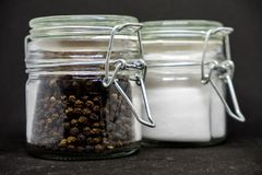 Βάζα του αλατιού και του πιπεριού στο μαύρο υπόβαθρο στοκ εικόνα