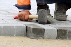 Βάζοντας τις πλάκες επίστρωσης στο τετράγωνο πόλεων, που επισκευάζει το πεζοδρόμιο Στοκ Φωτογραφία