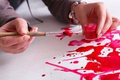 Βάζο βουρτσών και χρωμάτων στα χέρια Καλλιτέχνης που δημιουργεί τη ζωγραφική watercolor Στοκ Φωτογραφία