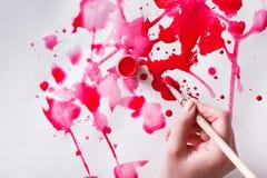 Βάζο βουρτσών και χρωμάτων στα χέρια Καλλιτέχνης που δημιουργεί τη ζωγραφική watercolor Στοκ Εικόνα