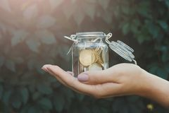 Βάζο γυαλιού εκμετάλλευσης χεριών με τα νομίσματα, πράσινο σκηνικό Στοκ φωτογραφία με δικαίωμα ελεύθερης χρήσης