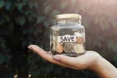 Βάζο γυαλιού εκμετάλλευσης χεριών με τα νομίσματα με την ετικέτα SAVE στοκ φωτογραφίες
