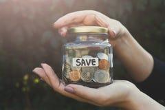 Βάζο γυαλιού εκμετάλλευσης χεριών με τα νομίσματα με την ετικέτα SAVE στοκ φωτογραφίες με δικαίωμα ελεύθερης χρήσης