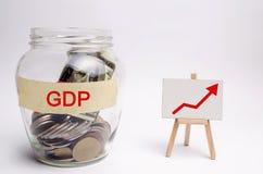 Βάζο γυαλιού με τα νομίσματα και την επιγραφή ΑΕΠ και επάνω στο βέλος Επιχείρηση, οικονομική, χρηματοδότηση, μισθός, κρίση Έννοια στοκ φωτογραφία με δικαίωμα ελεύθερης χρήσης