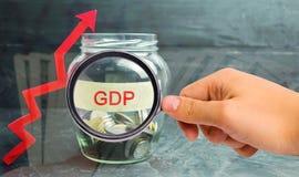 """Βάζο γυαλιού με τα νομίσματα και την επιγραφή """"ΑΕΠ """"και επάνω στο βέλος Επιχείρηση, οικονομική, χρηματοδότηση, μισθός, κρίση Οικο στοκ εικόνες με δικαίωμα ελεύθερης χρήσης"""