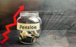 """Βάζο γυαλιού με τα νομίσματα και την επιγραφή """"σύνταξη """"και επάνω στο βέλος Συνταξιοδοτικές πληρωμές αύξησης Χρήματα αποταμίευσης στοκ φωτογραφία με δικαίωμα ελεύθερης χρήσης"""