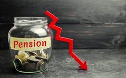 """Βάζο γυαλιού με τα νομίσματα και την επιγραφή """"σύνταξη """"και και κάτω βέλος Συνταξιοδοτικές πληρωμές πτώσης/μείωσης Αποχώρηση χρημ στοκ εικόνα"""