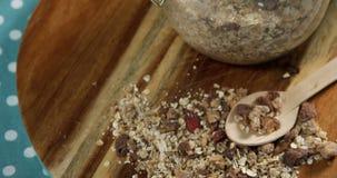 Βάζο γυαλιού του σπιτικών granola και του muesli με το κουτάλι στον ξύλινο πίνακα 4k φιλμ μικρού μήκους