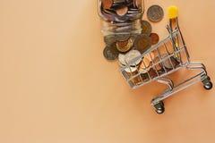Βάζο γυαλιού χρημάτων και μορφής νομισμάτων στο μίνι κάρρο ή το καροτσάκι αγορών στοκ φωτογραφία με δικαίωμα ελεύθερης χρήσης