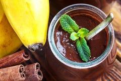 Βάζο γυαλιού με την πουτίγκα σοκολάτας ή mousse με τα φρέσκα ραβδιά μπανανών, μεντών και κανέλας πέρα από έναν ξύλινο πίνακα γλυκ Στοκ εικόνα με δικαίωμα ελεύθερης χρήσης